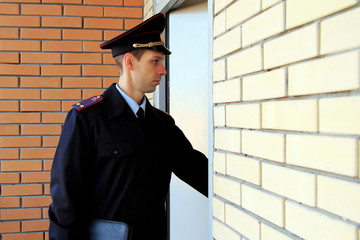 Russian policeman officer in the uniform of Russian police with leather portfolio in hand. Police lieutenant colonel in the service. Honest police concept. Copy space