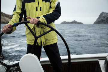 A sailing yacht skipper is at the helm. Close-up. It's cold, waves.