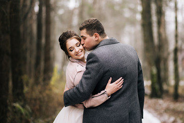 Portrait of happy young loving newlyweds.  The groom kisses the bride on the forest alley. Wedding day