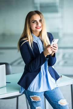 Business woman sending message with smartphone in office