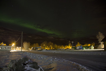 The northern lights (aurora borealis) rising behind a mountain in a small village in the north of Norway. In the middle of winter with snow covering the streets.