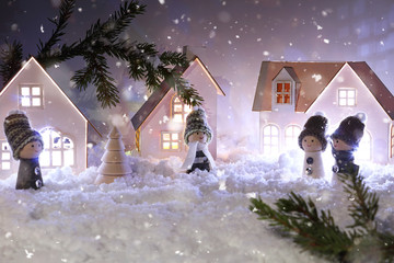 Photo sur Plexiglas Lilas Christmas decor for children. Christmas fairy tale on a snowy background. Cardboard houses with Christmas garland. Selective focus layout.