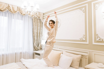 Beautiful young girl in Golden pajamas in a luxurious room with stylish hair and makeup lying jumping and dancing on the bed. Bride's morning