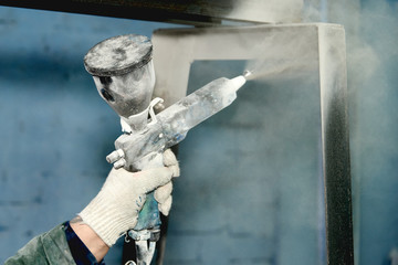 A man produces powder paint metal products.