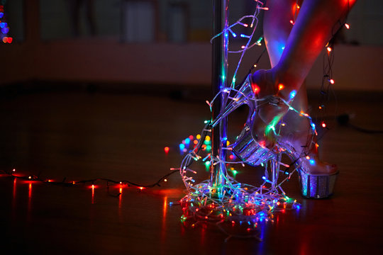 Female legs in Strip-shoes dancing on a pole silver shoes wrapped by bunch of Christmas lights
