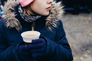 Young girl drinking popular hot non-alcoholic beverage, called in German language. Favourite children hot drink on Christmas markets in Switzerland and in german-speaking countries. Keeping warm at co