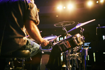 man from behind playing drums at concert