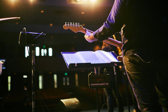 man from behind playing electric guitar at concert