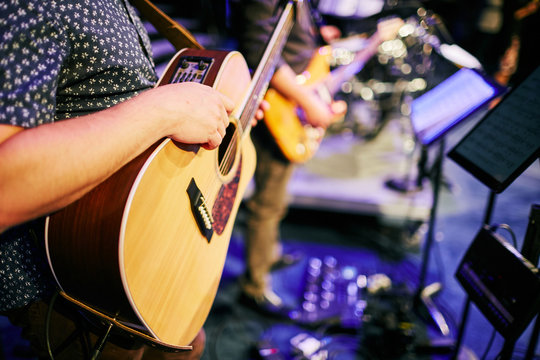 man waiting to play acoustic guitar at concert