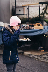 Young girl eating freshly prepared crepes which are thin pancakes with chocolate spread filling outside at Christmas market. Popular warm street food in Switzerland especially in winter time. Swiss fo