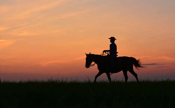 Cowboy in hat riding horse on colorful cloudy sky at sunset. Silhouette of  cowboy travel in wild west mountain like western film background