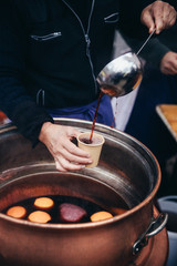 Pouring hot mulled wine, called Glühwein in German language, into a paper cup with a huge kitchen spoon. Favourite hot beverage at Christmas markets in Switzerland and in german-speaking countries. Ke
