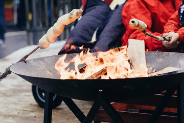 Roasting twist bread on open fireplace. Popular street food and outdoor activity on christmas markets and in winter time in Switzerland.