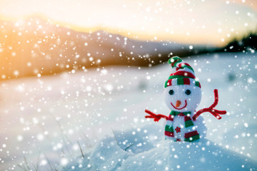 Small funny toy baby snowman in knitted hat and scarf in deep snow outdoor on blurred mountains landscape and falling big snowflakes background. Happy New Year and Merry Christmas greeting card theme.