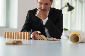 Worried serious businessman sitting at his desk stopping domino effect
