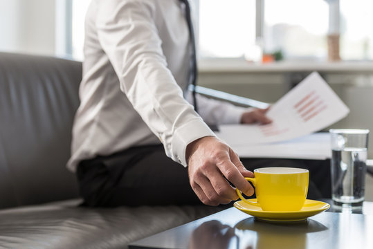 Businessman sitting in his office couch reaching for his yellow coffee cup