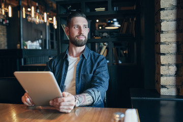 Modern hipster businessman drinking coffee in the city cafe during lunch time and working on tablet