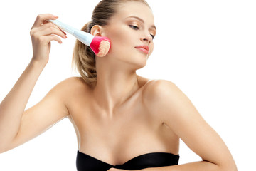 Attractive girl applies dry cosmetic on her face using makeup brush on white background. Youth and skin care concept