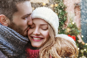 Young man kissing happy smiling woman on cheek. Cute young couple  posing in street. Christmas background
