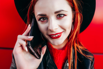 Young stylish hipster girl with red hair talking on the phone