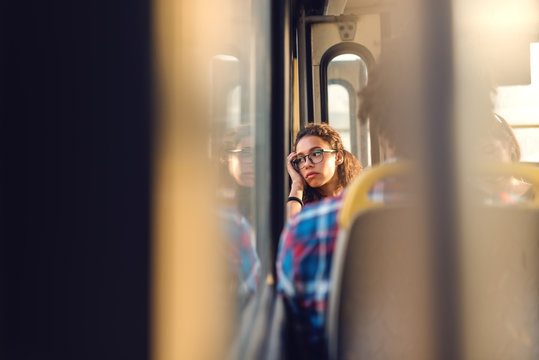 Thoughtful girl looking through window while sitting in public transportation.