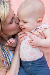 Baby girl being kissed by her mother