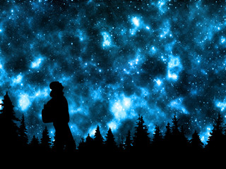 Person with backpack watching the stars in night sky above the pine forest