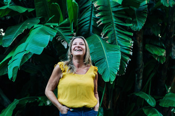Smiling woman by leaves of palm tree