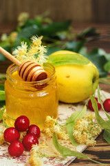 Open glass jar of liquid honey, apple and honey dipper, bunch of linden flowers