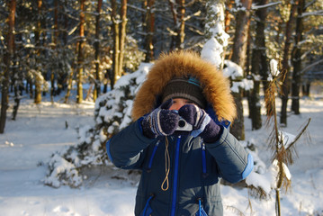 Boy with a digital camera taking pictures outdoor