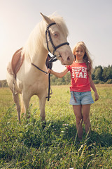 A young girl and white pony horse in countrysinde, Lithuania