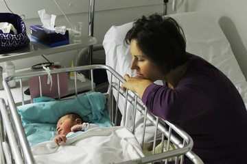 Mother looks with tenderness on her born daughter