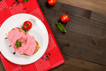 Sandwich with pink paste and tomato on the plate
