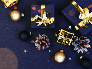 Merry Christmas and Happy New Year. Golden Christmas decorations and gift boxes on black background, flat lay photo, Xmas greeting card, banner