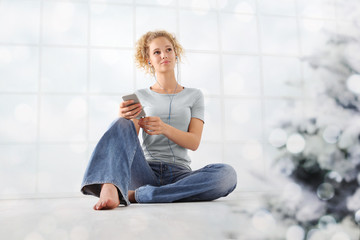 Merry Christmas concept young woman listens to christmas songs from her mobile phone with ear phones sitting at home with christmas tree in living room isolated on white window background