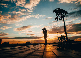 Man taking a picture at sunset