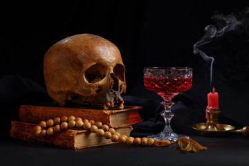 A skull, a rosary, a glass of wine and an unlit candle