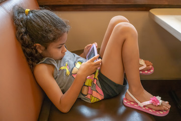 The young school girl nestled in a booth focused on playing a game on mommies smartphone.