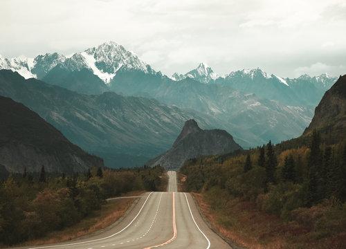 Looking down the road at snowy peaks