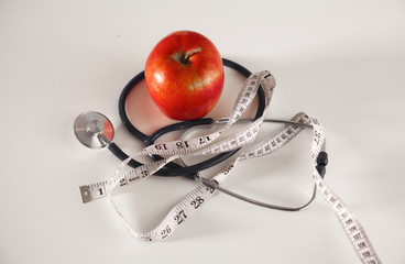 Apple, measuring tape and a stethoscope on the table