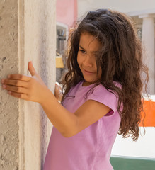 A young girl with long curly hair hides behind a wall holding on with both hands.