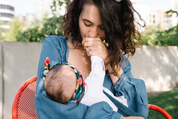 Mother kissing baby's hand while she breastfeeds her
