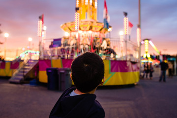 Young boy looking at an amusement park ride