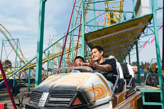 Father and son on an amusement park ride