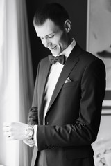 the morning of the groom, a handsome guy in a suit with a bow tie