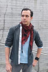 Handsome trendy man in shirt and neck kerchief standing on street looking away