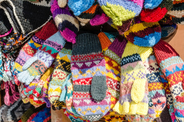 Multicolored hand-knitted woolen mittens and gloves on the market