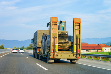 Truck trailer transporter and hauler carrying tractor on road Slovenia