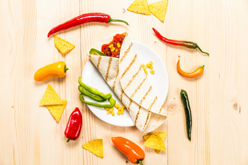 Stuffed colorful tortilla on a wooden background