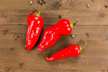 Three red chilli peppers on a wooden background